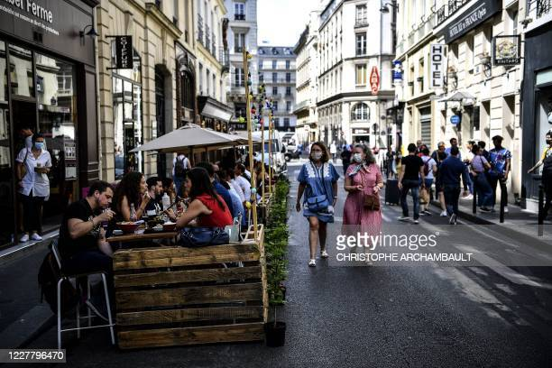People have lunch at the extended terrace of a restaurant made of wooden pallets in Paris on July 23 in respect for social distancing due to the...