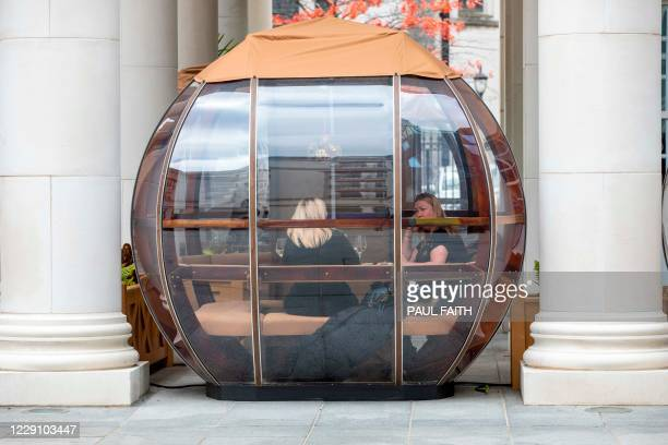 People have lunch in food bubble outside a restaurant in Belfast on October 16 as Northern Ireland imposes tighter coronavirus restrictions on the...