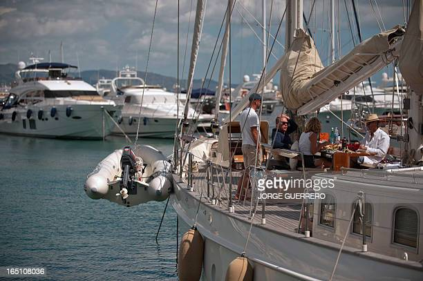 People have lunch on a boat in Puerto Banus near Marbella on March 30 2013 AFP PHOTO / JORGE GUERRERO