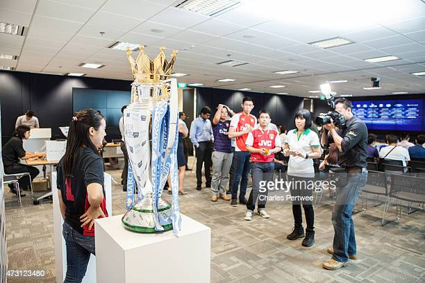 People have their photo taken with the Barclays Premier League trophy and the Barclays Asia Trophy before a QA at the Barclays office during the...