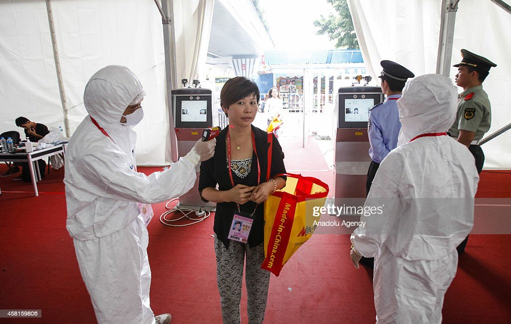 People have their temperature taken at the entrance of Canton Fair in Guangzhou, Guangdong province, October 30, 2014. Chinese authorities have identified the southern province of Guangdong, home to Asia's biggest African population, as a frontline in their efforts to prevent the deadly Ebola virus from entering mainland China.