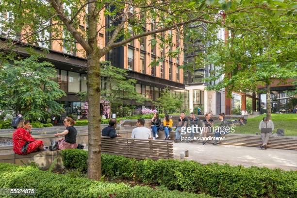 オフィスに囲まれた広場に休憩を持つ人々 - キングスクロス駅 ストックフォトと画像