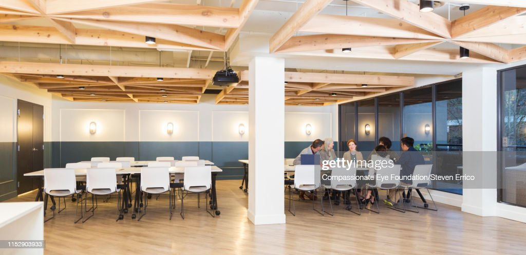 People having business meeting in open plan office : Stock Photo