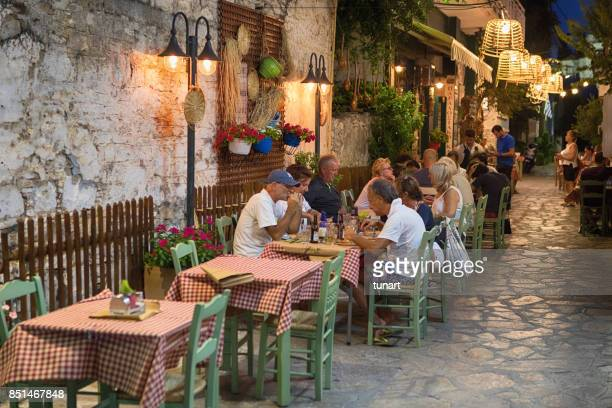 people having dinner on a street of pythagoreion, samos, greece - samos stock photos and pictures