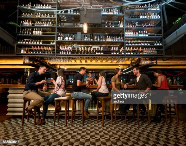people having drinks at a bar - pub stock pictures, royalty-free photos & images