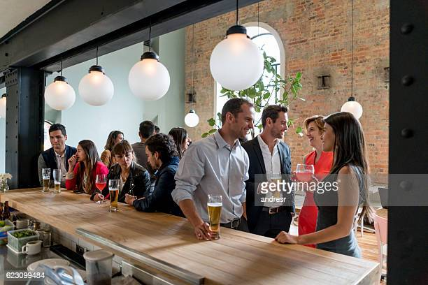 people having drinks at a restaurant - comptoir de bar photos et images de collection