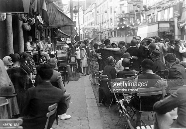 People having drinks on a cafe terrace looking at dancers in the street on Bastille Day, on July 14, 1929 in Paris, France.