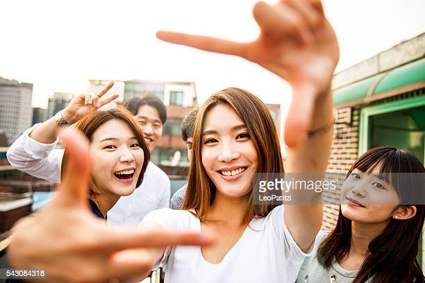 people having fun, taking a selfie all together at party - korean ethnicity stock pictures, royalty-free photos & images