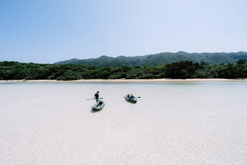 People having fun with inflatable rafts in shallow tropical lagoon, Ishigaki Island, Japan - gettyimageskorea