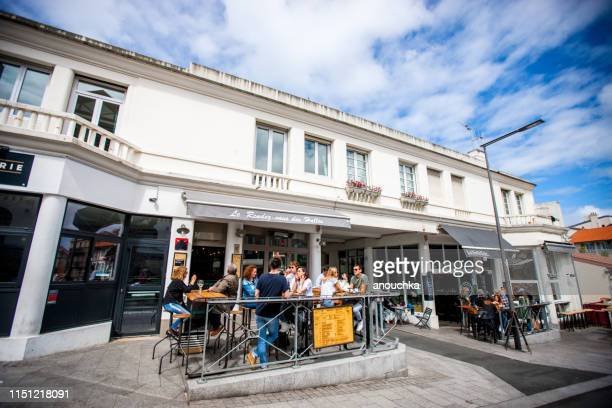 people having lunch in a cafe in front of market hall, biarritz, france - biarritz stock pictures, royalty-free photos & images