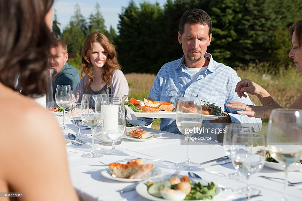 People having meal at table in a field : Stock Photo