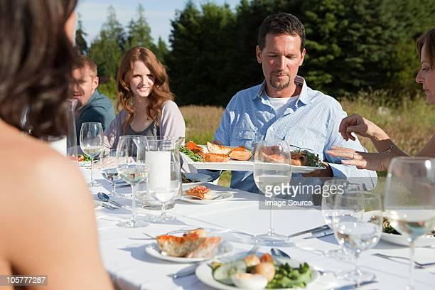 Personen, die Mahlzeit am Tisch in einem Feld
