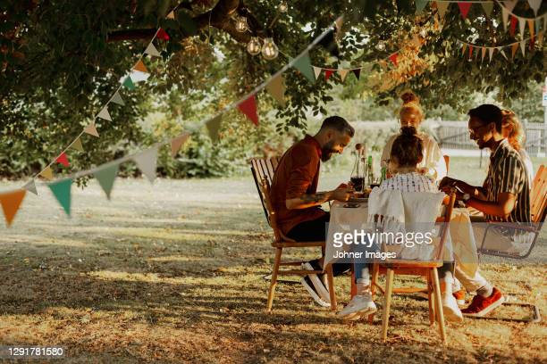 people having meal in garden - garden party stock pictures, royalty-free photos & images