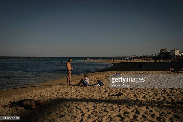 People having sunbath in the foreground which separates Varosha from the accessible area of Famagusta Bay.