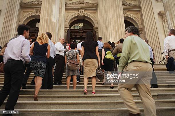 People head back into their buildings in lower Manhattan after being evacuated following an earthquake on August 23 2011 in New York City The...