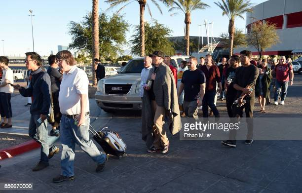 People head to buses as they leave the Thomas Mack Center after a mass shooting at a country music festival on October 2 2017 in Las Vegas Nevada...