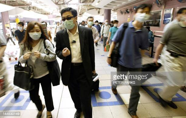 People head to Hong Kong immigration control at the Lo Wu border point to cross into China while wearing masks to protect against SARS, 22 April...
