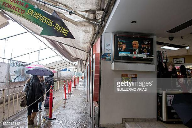 People heading to the United States walk at San Ysidro pedestrian crossing brigde as a sreen shows US President Donald Trump during his inauguration...