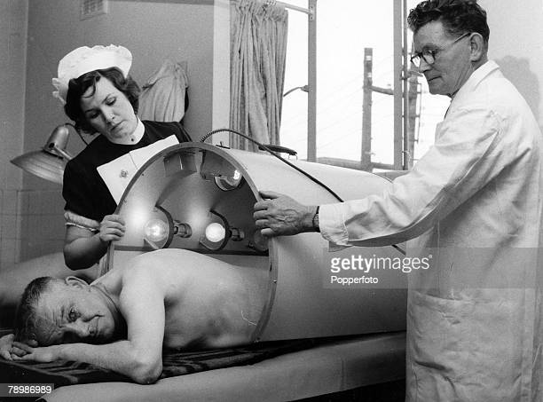 1954 Great Britain A doctor and a nurse about to give therapy and lamp treatment to a mine worker suffering from back problems a common complaint of...