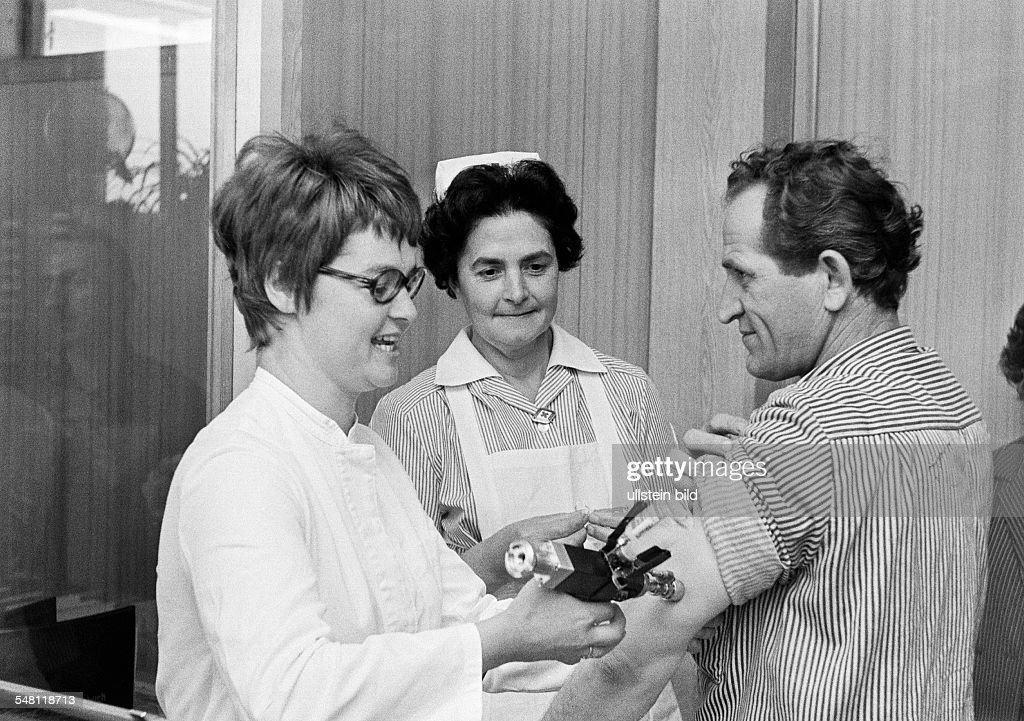 people, health, precaution, injection, influenza virus vaccination, female doctor, aged 30 to 40 years, nurse, aged 40 to 50 years, patient, man, aged 45 to 55 years - 30.09.1971 : News Photo