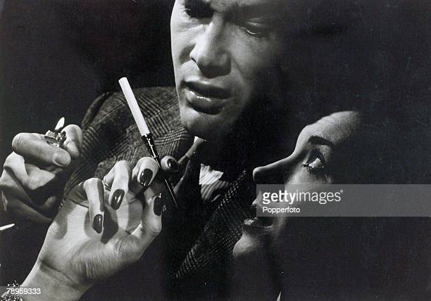 1949 A woman holding a cigarette in it's holder about to be offered a light by a man