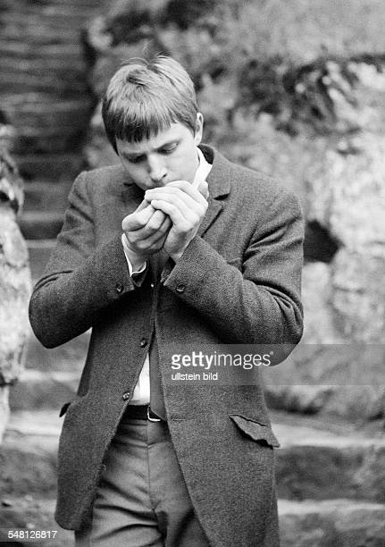 people health young man lights a cigarette aged 20 to 25 years Reiner