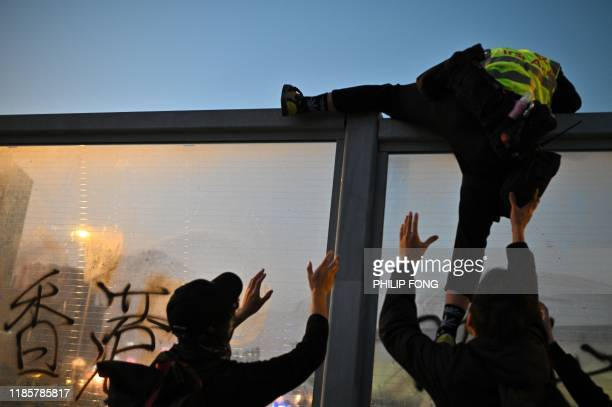 TOPSHOT People help a first aid volunteer climb a noise barrier to avoid police following a prodemocracy march from the Tsim Sha Tsui district to...