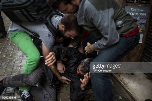 People help a man injured by a rubber bullet fired by Spanish police officers outside the Ramon Llull polling station in Barcelona October 1 2017...