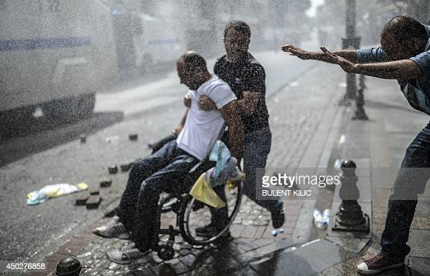 People help a man on a wheelchair during a clash between Kurdish protestors and Turkish riot policemen on June 8 in the Bagcilar district of Istanbul...