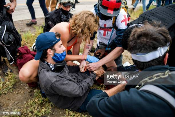 People help a man who was shot after a car sped through a crowd of protestors marching on I225 to protest the death of Elijah McClain on July 25 2020...