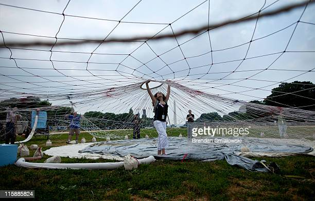 People help raise a net for an American Civil Warera balloon during a demonstration on the National Mall June 11 2011 in Washington DC Reenactors...
