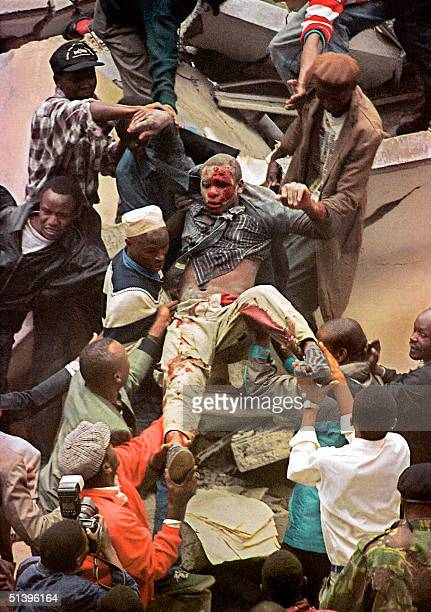 People help rescue one of the people injured when a bomb exploded near the US embassy and a bank in Nairobi 07 August 1998 killing at least 60 people...
