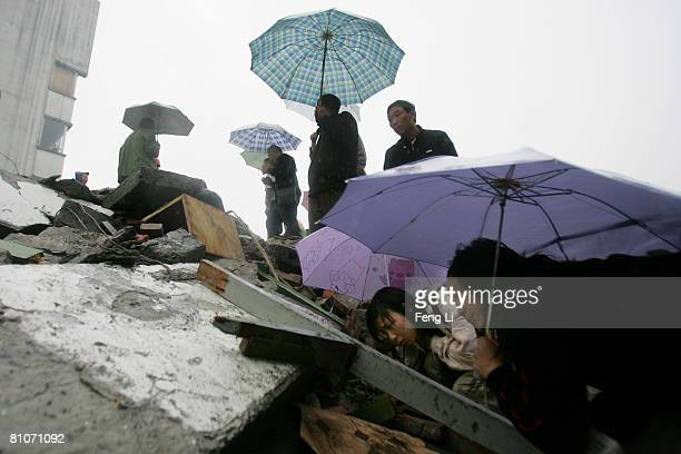 People help search for victims in the debris of a building that collapsed 96km from Wenchuan the epicenter of the earthquake May 13 2008 in Sichuan...