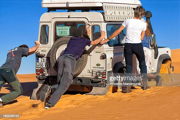 People help the 4x4 to get out sand,