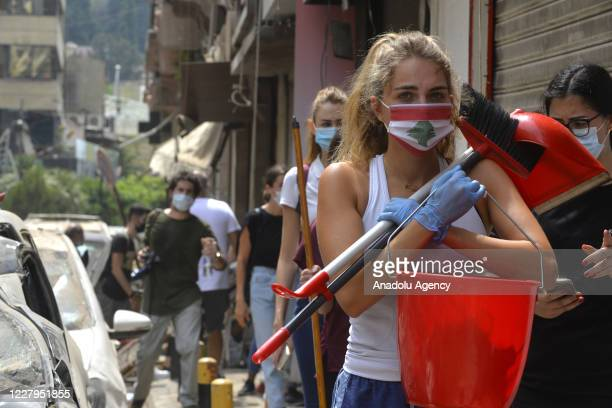 People help to clean debris after a fire at a warehouse with explosives at the Port of Beirut led to massive blasts in Beirut, Lebanon on August 07,...