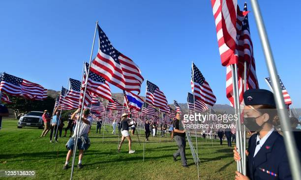 People help unfurl American flags to commemorate the 20th anniversary of 9/11 during the annual Waves of Flags display and remembrance at Pepperdine...