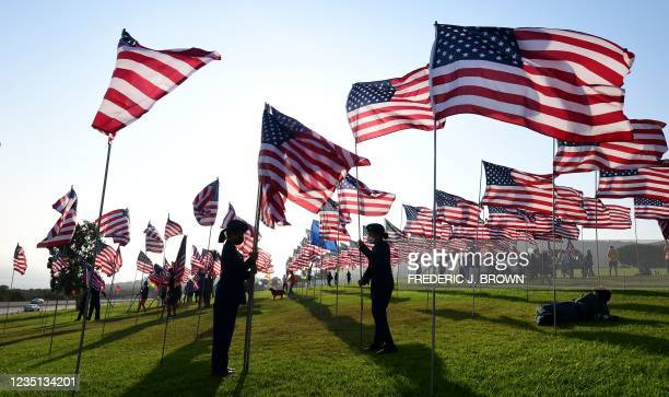 People help with the display of US flags to commemorate the 20th anniversary of 9/11 with the annual Waves of Flags display and remembrance at...