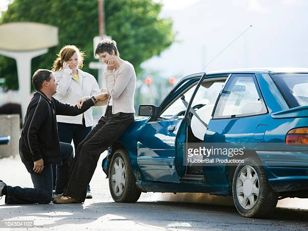 people helping a woman after a car accident - airbag stock photos and pictures