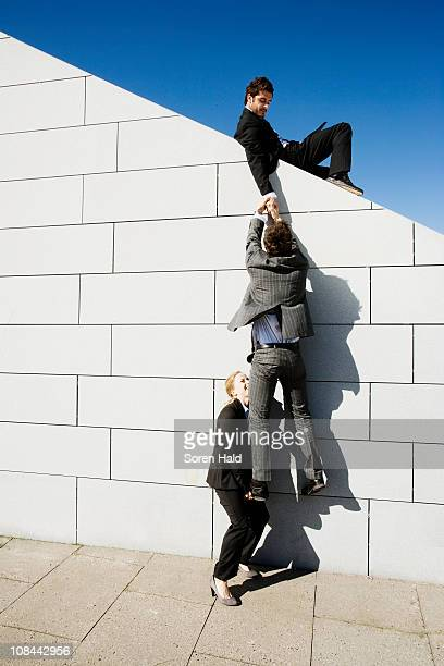 2 people helping man over wall