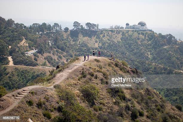 People hike along a ridge overlooking the Griffith Observatory where vegetation is quickly drying out in Griffith Park on March 29 2015 in Los...