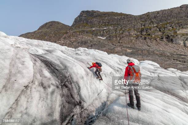 people hiking on snow covered mountains at jostedalsbreen - extreme weather stock photos and pictures