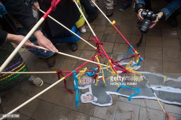 People hit a paper cutout of US President Donald Trump in front of Trump International Hotel during the Native Nations Rise protest on March 10 2017...