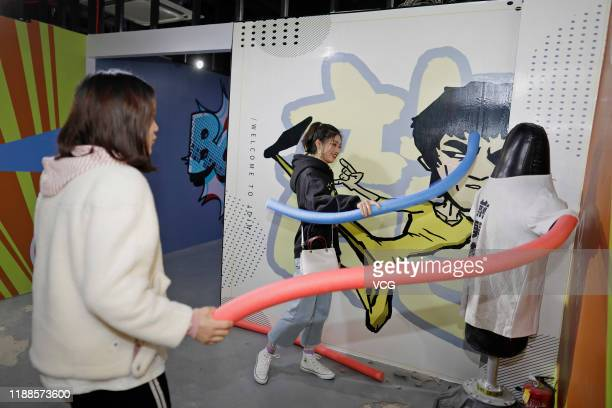 People hit a punching bag with words reading 'exboyfriend' at a stressrelief museum on November 18 2019 in Suzhou Jiangsu Province of China