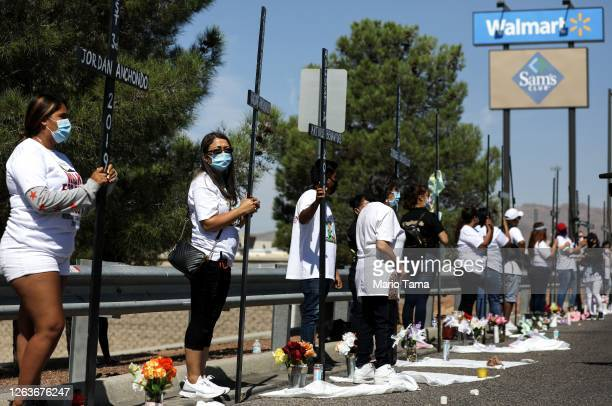 People hold 23 crosses in front of a Walmart honoring those killed in the Walmart shooting which left 23 people dead in a racist attack targeting...