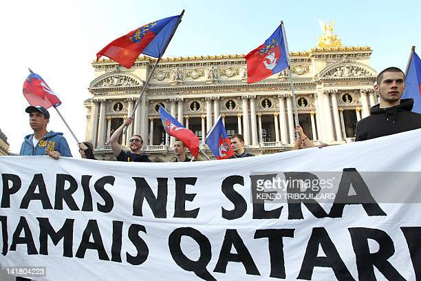 """People hold a banner and flags of Paris' city during a demonstration of the Bloc Identitaire to protest against the fact that """"Qatar buys France"""" on..."""