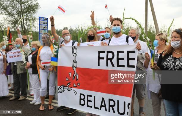 People hold a banner as they form a human chain from Vilnius to Medininkai along the border with Belarus to show solidarity with the Belarussian...