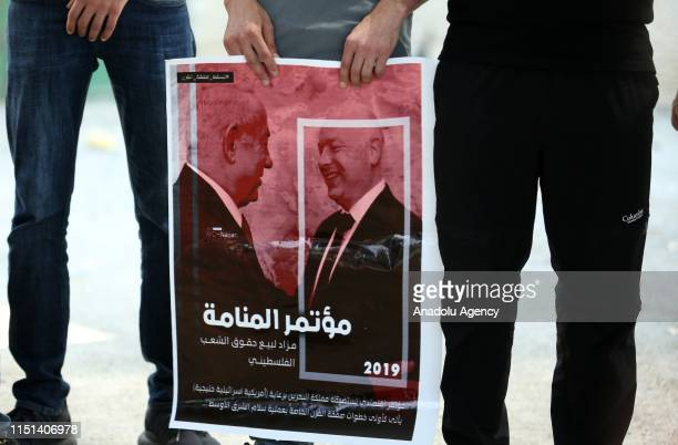 People hold a banner as they gather for a demonstration against a conference which is the Peace to Prosperity US economic workshop scheduled for June...