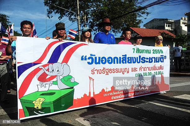 People hold a banner as they march during a campaign encouraging the public to vote in the upcoming referendum on Thailand's draft constitution in...