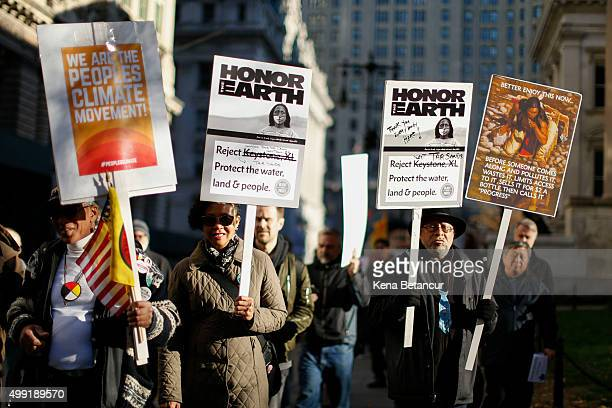 People hold a banner as they take part in a global climate march near City Hall on November 29 2015 in New York City The protest is part of an...