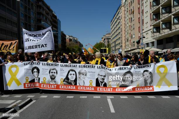 People hold a banner depicting portraits of Catalan exiled politicians during a demonstration to support Catalan proindependence jailed leaders and...